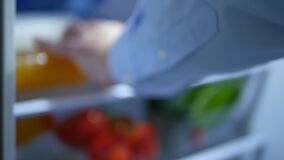Blurred Image of a Man Opening the Door of Refrigerator Full of Food and Putting Inside a Bottle of Orange Juice to Cool