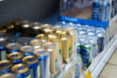 Blurred image of packaging with canned beer on the store shelf