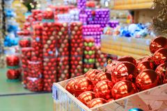 Blurred image of red balls in the box and Christmas and New Year decorations in the store, defocused background of the market stock image