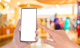 Blurred image of shopping mall and people . Male hand is holding a modern touch screen phone and Blurred image of shopping mall Royalty Free Stock Photography