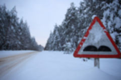 Blurred image snowy winter forest route. traffic sign rough road Stock Image