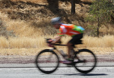 A blurred image of a speeding bike rider. A blurred image of a road bicycle moving down a country road Royalty Free Stock Photography