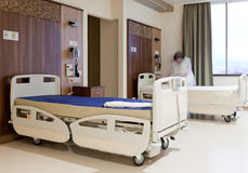Staff fixing hospital bed. Blurred image of staff member in medical uniformn fixing hospital bed Stock Photography