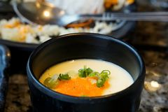 Blurred image of Steamed egg with scallion sliced in big bowl on able in restaurant ready to eat, Kai thoon is Thai traditional. Chawanmushi, Clean food of royalty free stock photo
