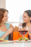Blurred image of two teenage girls talking in cafe. Royalty Free Stock Photography
