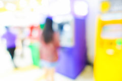 Blurred image of woman in bank use ATM machine Royalty Free Stock Photo