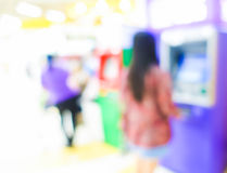 Blurred image of woman in bank use ATM machine Stock Image