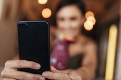 Woman taking a selfie for her blog. Blurred image of a woman taking a selfie with a smoothie placed on the table using a mobile phone. Food blogger shooting Royalty Free Stock Photography