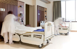 Fixing hospital beds room. Blurred images of staff members changing hospital bed sheets in modern equipped room Royalty Free Stock Photos