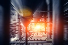 Blurred industrial brewery plant or factory with steel pipes ant vats or tanks for background, fast moving effect with sunlight. Toned royalty free stock photography
