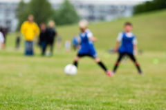 Blurred kids on soccer pitch Royalty Free Stock Photos