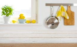 Blurred kitchen interior background with wooden table top in front Royalty Free Stock Image