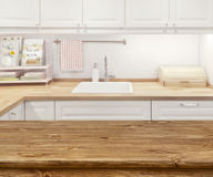 Blurred kitchen interior with wooden dinning table in front stock photography