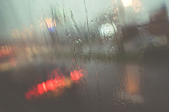 Blurred light of cars seen through wet windshield with some raindrops Stock Photos