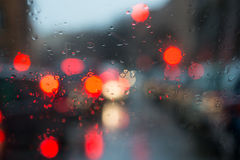 Blurred light through a wet windshield. Blurred light of cars seen through  a wet windshield with some raindrops on it in the early morning of a rainy day Royalty Free Stock Images