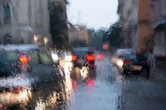 Blurred light through a wet windshield. Blurred light of cars seen through  a wet windshield with some raindrops on it in the early morning of a rainy day Stock Photos