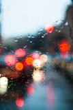 Blurred light through a wet windshield. Blurred light of cars seen through  a wet windshield with some raindrops on it in the early morning of a rainy day Royalty Free Stock Photos