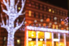Blurred lights of the Christmas and New Year illuminations on the background of architecture, abstract bokeh, defocused. Blurred lights of the urban Christmas royalty free stock photo