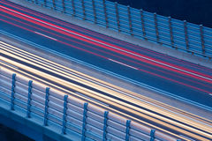 Blurred lights of vehicles. Driving on a viaduct with wind barriers, long exposure Stock Photos