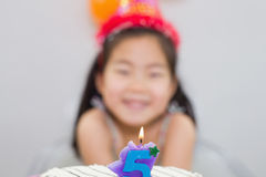 Blurred little girl with lit candle on birthday cake Royalty Free Stock Photography