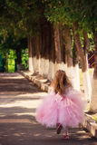 A Blurred litttle Girl running in the garden in Summer Sunset i Royalty Free Stock Images