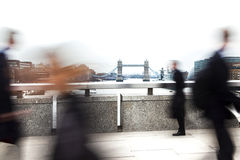 Blurred London commuters. High key photograph of motion blurred bankers / commuters from the City walking over the River Thames during the  rush hour in London Royalty Free Stock Images