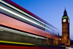 Blurred London double-decker bus passes Big Ben. A London double-decker bus passes in front of Big Ben and the Houses of Parliament at night in London, England Royalty Free Stock Photo