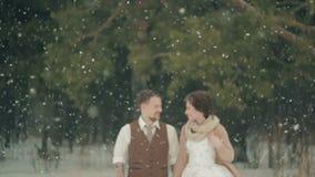 Blurred loving couple walking in winter christmas snowfall stock video