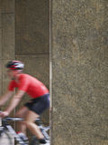 Blurred Man Cycling Between Pillars In Portico Royalty Free Stock Image
