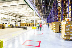 Blurred man inspecting boxes in distribution warehouse. Abstract view, workers quickly walk through the warehouse Royalty Free Stock Photos