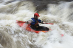 Blurred Man kayaking in river. Side view of a blurred man kayaking in rough river Stock Images