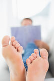 Blurred man reading a book with focus on bare feet Stock Photography