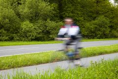 Blurred Man Riding Bicycles Along a Country Road Royalty Free Stock Photos