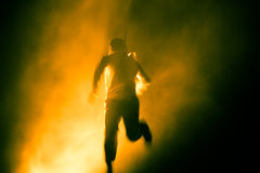 Blurred man running in the rain to a yellow light Royalty Free Stock Photo