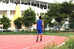 Blurred man running track for in the stadium. Royalty Free Stock Photos