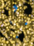 Blurred background of yellow Christmas lights at night. Blurred mass of yellow and some blue twinkle lights at night stock photography
