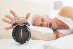 Blurred mature man extending hand to alarm clock Stock Image