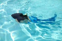 Real Mermaid Blurred. Real blurred mermaid swimming in light blue water Stock Image