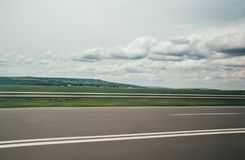 Blurred motion blur photo of autobahn railroad . Huge white clouds above.  Royalty Free Stock Photography