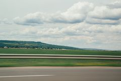Blurred motion blur photo of autobahn railroad . Huge white clouds above Stock Photo