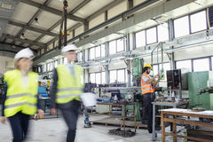 Blurred motion of business people with manual worker in background at industry royalty free stock photography