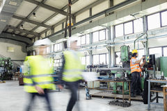 Blurred motion of business people walking with manual worker in background at industry.  Royalty Free Stock Photo