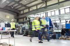 Blurred motion of business people wearing reflective clothing walking in metal industry stock images