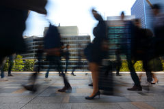 Blurred motion of businessmen and businesswomen commuting to work during busy rush hour in Tokyo, Japan Stock Images
