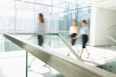 Blurred motion of businesswomen walking at office hallway stock images