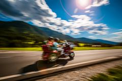 Tricycle Blurred motion Bikers on the road. Blurred motion Couple Bikers riding a tricycle on the road stock photo