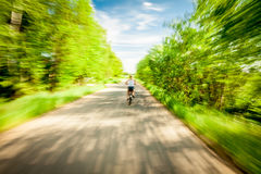 Blurred motion of cycling  woman. Young female riding  on her bike with motion blur on country road along  green trees towards blue sky Royalty Free Stock Images