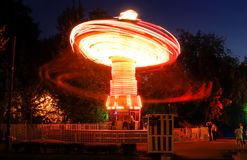 Blurred motion effect around of brightly illuminated rotating high speed carousel merry-go-round. Late in the evening in an amusem Royalty Free Stock Photo