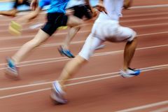 Blurred motion group runners. Sprinters running on track stadium Royalty Free Stock Photo