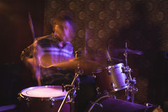 Blurred motion of male drummer in nightclub. Blurred motion of male drummer performing in nightclub Royalty Free Stock Photos